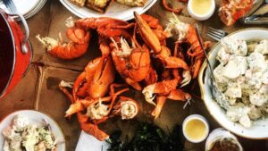 Overhead view of dishes of food, with lobster in the center.