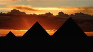 Silhouettes of three pyramids at sunset.