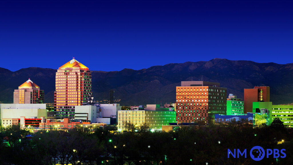 Skyline view of downtown Albuquerque brightly lit, with the Sandias in the background.