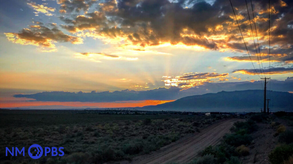 View of a New Mexican sunset, with rays shimmering through clouds and a mountain.