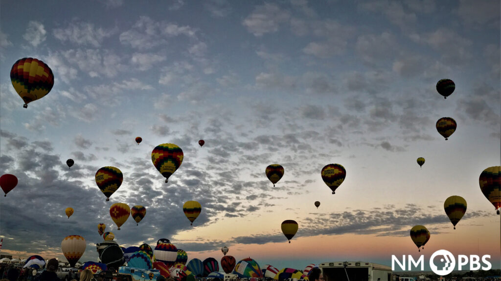 Several hot air balloons take off into the sky at sunrise.