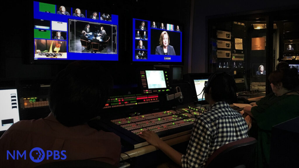 Interior view of three people working within the NMPBS studio control room.
