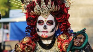 A person in skull makeup and wearing ceremonial regalia.