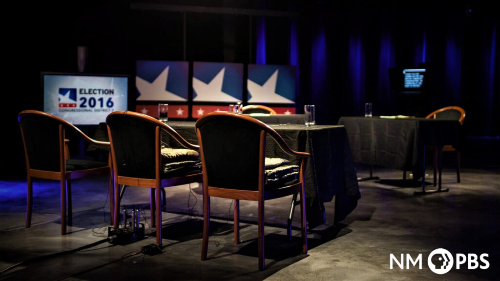 """The NMPBS studio with tables and chairs setup, and with a screen reading """"ELECTION 2016""""."""