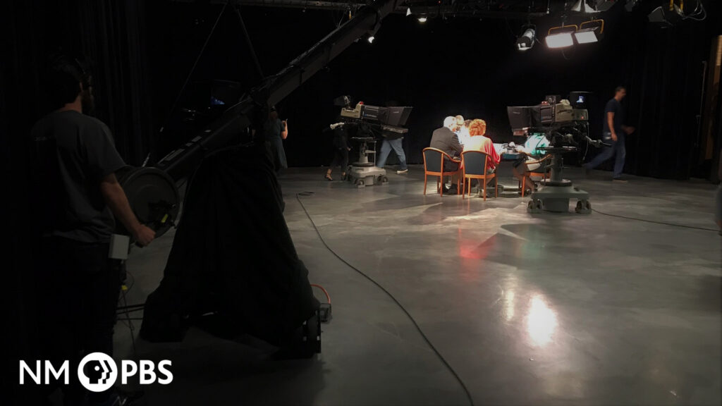 Interior view of the NMPBS studio, with someone manning a jib and a few others gathered at a brightly-lit table.