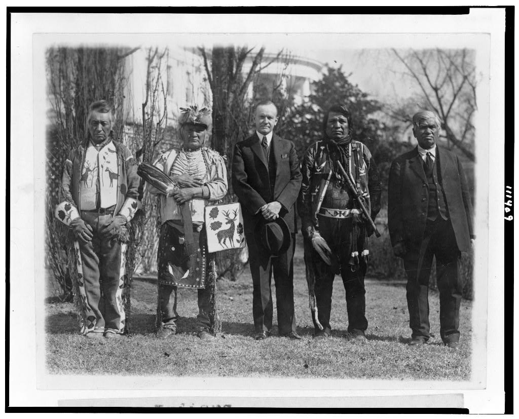 A man in a suit is flanked by Indigenous representatives in assorted regalia, including one in a suit.