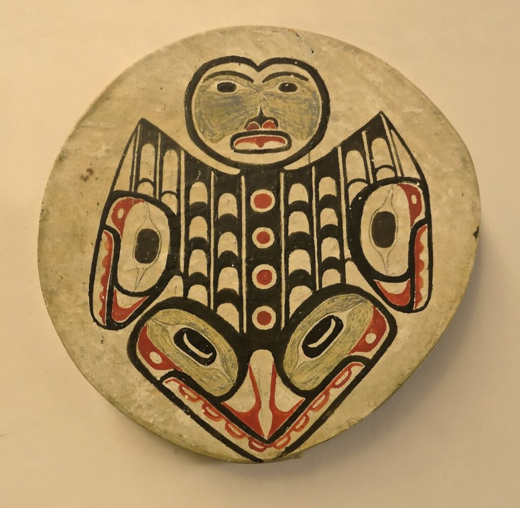 A tribal drum hangs on a wall.