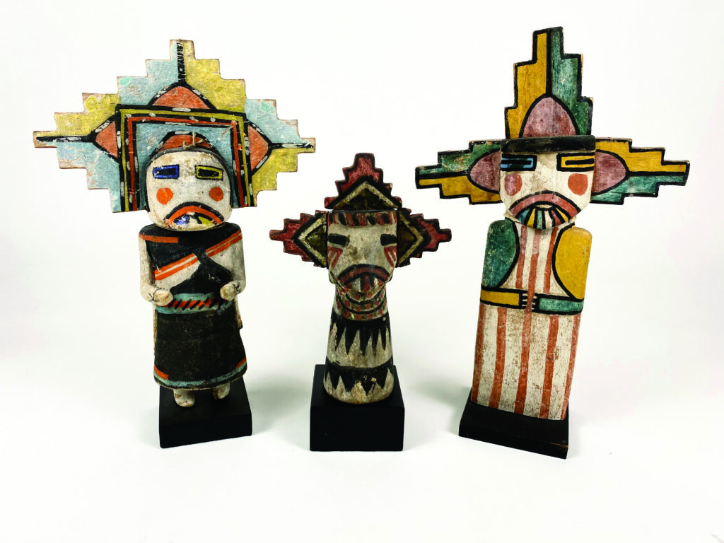 Three colorful tribal statues stand next to each other.
