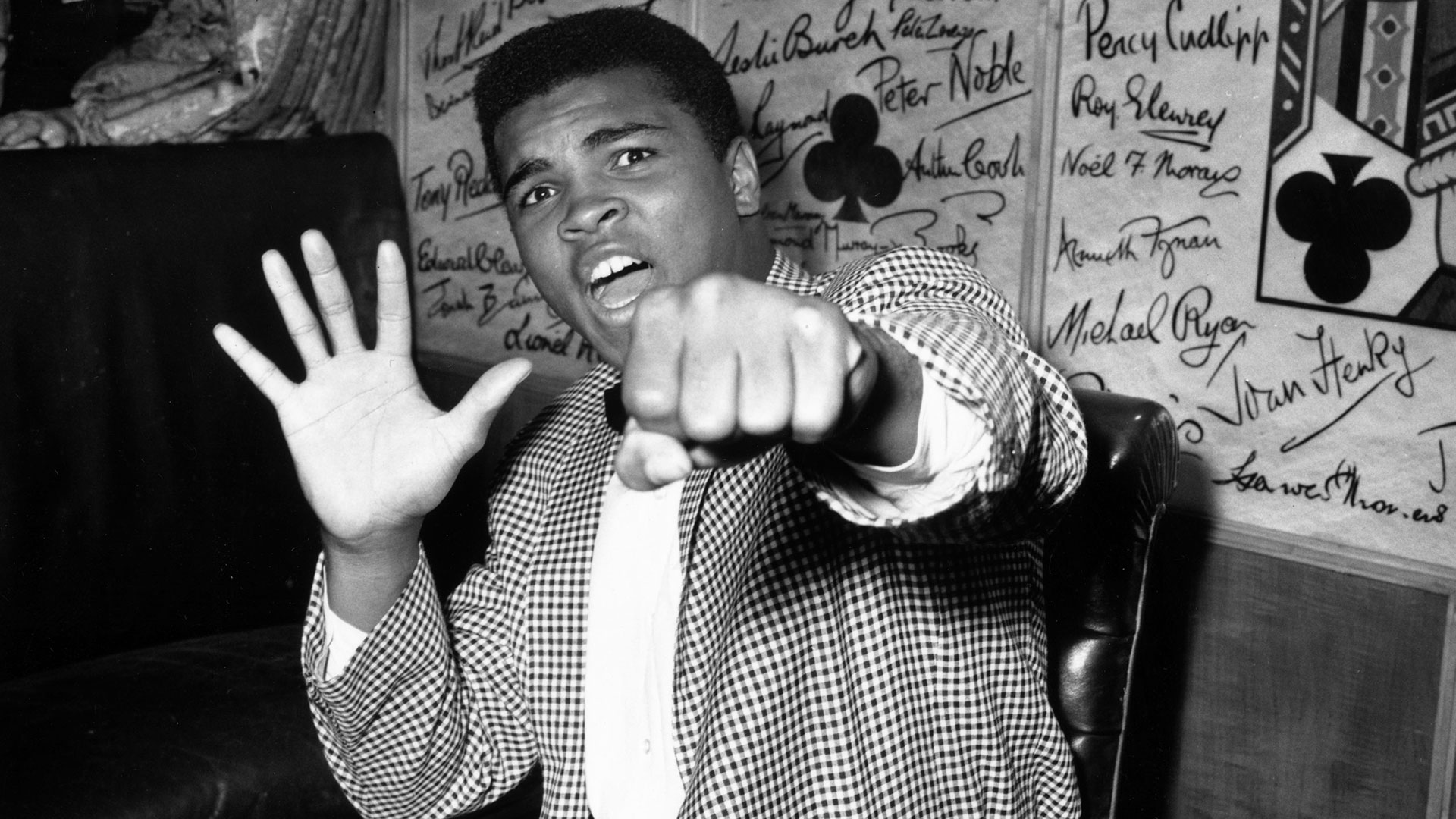 Muhammad Ali holding up a fist and five fingers on the other hand